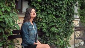 Mooie jonge rond en meisjeszitting op een bank, wachten die, die eruit zien genieten van stock videobeelden