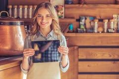 Mooie jonge serveerster met gadget royalty-vrije stock foto's