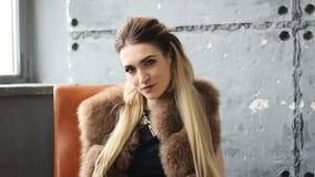 Mooie jonge sexy blondevrouw die een zwart kledings modieus ontwerp en een modieuze bontjas dragen stock video
