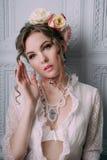 Mooie jonge sexy die vrouw, haar met bloemen wordt verfraaid Perfecte Make-up Schoonheidsmanier eyelashes De studio retoucheerde  stock fotografie