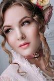 Mooie jonge sexy die vrouw, haar met bloemen wordt verfraaid Perfecte Make-up Schoonheidsmanier eyelashes De studio retoucheerde  royalty-vrije stock afbeeldingen
