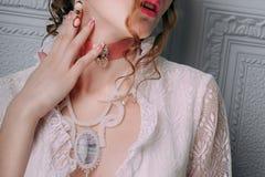 Mooie jonge sexy die vrouw, haar met bloemen wordt verfraaid Perfecte Make-up Schoonheidsmanier eyelashes De studio retoucheerde  stock foto's
