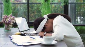 Mooie jonge spannings Aziatische vrouw die aan laptop thuis werken terwijl ongelukkige het gebruiken smartphone in woonkamer stock videobeelden