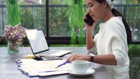 Mooie jonge spannings Aziatische vrouw die aan laptop thuis werken terwijl ongelukkige het gebruiken smartphone in woonkamer stock video