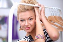 Mooie jonge stilist dichtbij rek met hangers royalty-vrije stock foto