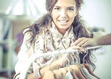Mooie jonge stilist dichtbij rek met hangers royalty-vrije stock afbeeldingen