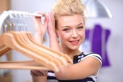 Mooie jonge stilist dichtbij rek met hangers in bureau Royalty-vrije Stock Afbeeldingen