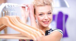 Mooie jonge stilist dichtbij rek met hangers in bureau Royalty-vrije Stock Foto's
