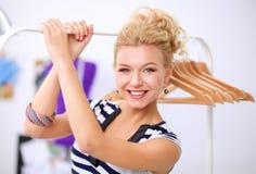 Mooie jonge stilist dichtbij rek met hangers in bureau royalty-vrije stock fotografie