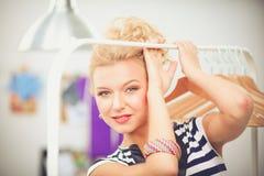 Mooie jonge stilist dichtbij rek met hangers in bureau royalty-vrije stock afbeelding