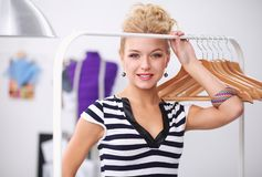 Mooie jonge stilist dichtbij rek met hangers in bureau stock foto's
