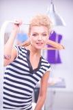 Mooie jonge stilist dichtbij rek met hangers in bureau stock foto