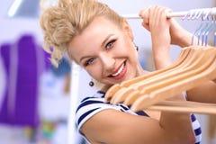 Mooie jonge stilist dichtbij rek met hangers in bureau royalty-vrije stock foto