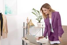 Mooie jonge stilist die met laptop in studio werken stock afbeelding