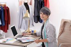 Mooie jonge stilist die met laptop in studio werken royalty-vrije stock foto