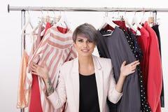 Mooie jonge stilist met kleren op hangers royalty-vrije stock foto's