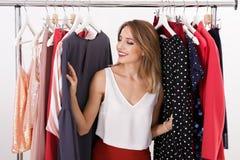 Mooie jonge stilist met kleren op hangers royalty-vrije stock afbeeldingen