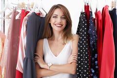 Mooie jonge stilist met kleren op hangers stock foto