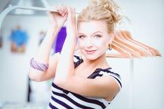 Mooie jonge stilistvrouw dichtbij rek met hangers Stock Foto