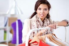 Mooie jonge stilistvrouw dichtbij rek met hangers Royalty-vrije Stock Fotografie