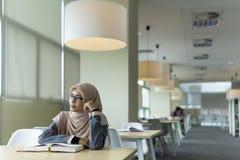 Mooie jonge student in de bibliotheek stock afbeelding