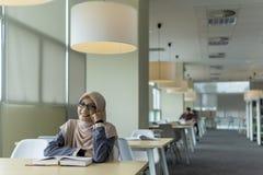 Mooie jonge student in de bibliotheek stock fotografie