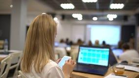 Mooie Jonge Student Uses Laptop terwijl het Luisteren aan een Lezing bij de Universiteit Vrouwelijke student die mobiele telefoon stock videobeelden