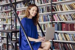Mooie jonge studentzitting op treden in de bibliotheek, die aan laptop werken Vrouw die blauwe kleding, reusachtig boekenrek drag stock afbeelding