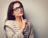 Mooie jonge toevallige vrouw die in glazen met vinger denken und royalty-vrije stock foto