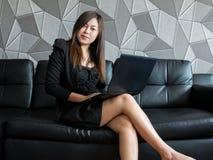 Mooie jonge van bedrijfs Azië vrouwenzitting op bank, die met laptop computer en slijtage het zwarte kostuum letten op aan camera Stock Foto's