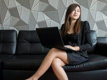 Mooie jonge van bedrijfs Azië vrouwenzitting op bank, die met laptop computer en slijtage zwart kostuum werken die kant opletten  Stock Afbeeldingen