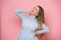 Mooie jonge volwassen gelukkige vrouw die en omhoog dichtbij roze muur glimlachen kijken stock foto's