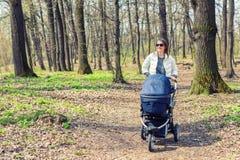 Mooie jonge volwassen vrouw die met baby in wandelwagen door bos lopen of park op heldere zonnige dag Gezonde Levensstijl royalty-vrije stock afbeelding