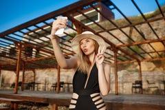 Mooie jonge vrolijke meisjesrust die bij ochtendstrand selfie maken Royalty-vrije Stock Afbeelding