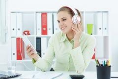 Mooie jonge vrolijke onderneemster het luisteren muziek in hoofdtelefoons op kantoor Royalty-vrije Stock Afbeeldingen