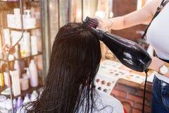 Mooie jonge vrouw bij de kappersalon Kapper die kapsel maken stock afbeelding