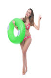 Mooie jonge vrouw in bikini het stellen met een grote groene rubberring Royalty-vrije Stock Afbeelding