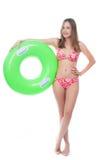 Mooie jonge vrouw in bikini het stellen met een grote groene rubberring Stock Afbeeldingen