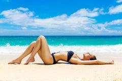 Mooie jonge vrouw in bikini op een tropisch strand Royalty-vrije Stock Foto's