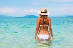Mooie jonge vrouw in bikini op het zonnige tropische strand Stock Afbeelding