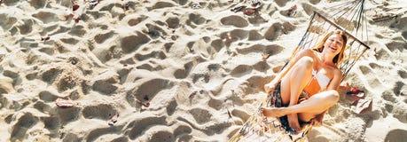 Mooie jonge vrouw in bikinibovenkant die in hangmat op het zandige strand en de vrolijke het lachen hoogste mening slingeren in c stock foto