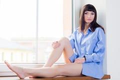 Mooie jonge vrouw in blauwe overhemdszitting op de venstervensterbank stock afbeeldingen