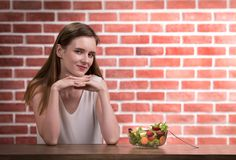 Mooie jonge vrouw in blije houdingen met saladekom royalty-vrije stock foto