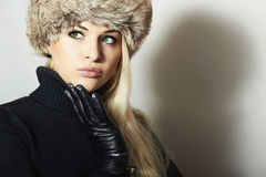 Mooie jonge vrouw in bonthoed Vrij blond meisje De Schoonheid van de de wintermanier Mooi Blond Meisje in Zwarte Leerhandschoenen Stock Fotografie