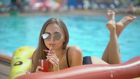 Mooie jonge vrouw in de zomer Bikinimeisje het ontspannen in tropisch zwembad Mooie jonge vrouw in de zomer bikini stock videobeelden
