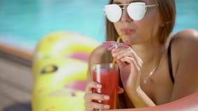 Mooie jonge vrouw in de zomer Bikinimeisje het ontspannen in tropisch zwembad vrouw die een verse cocktail drinken stock footage