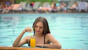Mooie jonge vrouw in de zomer Bikinimeisje het ontspannen in tropisch zwembad vrouw die een verse sinaasappel drinken stock video