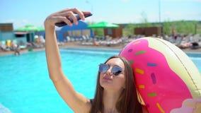 Mooie jonge vrouw in de zomer die selfies op smartphone nemen Bikinimeisje het ontspannen in tropisch zwembad E stock footage