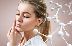 Mooie jonge vrouw dichtbij grote witte moleculeketting stock foto