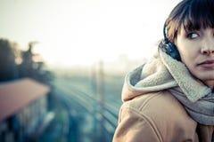 Mooie jonge vrouw die aan muziekhoofdtelefoons luisteren royalty-vrije stock foto